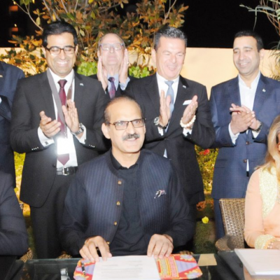 Bavarian Business Delegation to Pakistan, October 2018: Front: Ahsan Mehmood Baba, Politician and President Lions Club Chillianwala, Patricia Poetis, CEO, Life Fund Equity Invest and founder of Lions Club Chillianwala, signing an agreement of Patty's Child Clinics Pakistan with Aamir Mehmood Kiani, Federal Minister for National Health Services, Regulation and Coordination. In the background are Mr. Rieger, Head of Delegation, Murad Mehmood, Manager of Business Delegations, Honorary Consulate of the Islamic Republic of Pakistan, Prof. Dr. Dr. Walter Schmidt, Managing Director, InterMedia, Honorary Consul Dr. Poetis, Khurram Jameel, Managing Director & CEO, Siemens Healthineers, Sikander Mir- Kohler, Former Honorary Investment Counsellor, Board of Investment, Pakistan